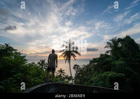 Silhouette di uomo che si erge da solo sulla collina con palme da cocco e gode di mare all'orizzonte in un tramonto. Concetto di vacanza e viaggio su un