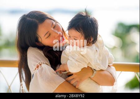 Giovane felice e bella donna asiatica coreana che gioca e tiene dolce adorabile bambina seduta al resort vacanze godendo di viaggio di vacanza estiva in Foto Stock