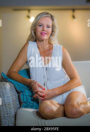 ritratto verticale stile di vita di bella e di classe donna bionda capelli sui suoi 40 seduta felice a casa soggiorno bere succo d'arancia seduta relaxe