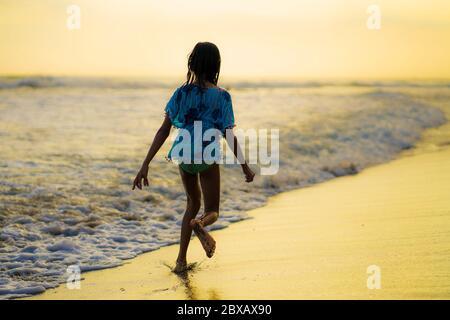 Indietro tracking gimbal colpo a piedi di 7 o 8 anni Asian ragazza indonesiana bambino corsa felice sulla spiaggia bella godendo vacanze estive in childho Foto Stock