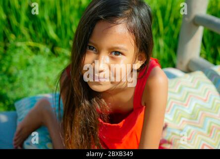 outdoor stile di vita ritratto di bella e dolce giovane ragazza sorridente felice e allegro il bambino con gli occhi meravigliosi e vestito in un abito rosso isola