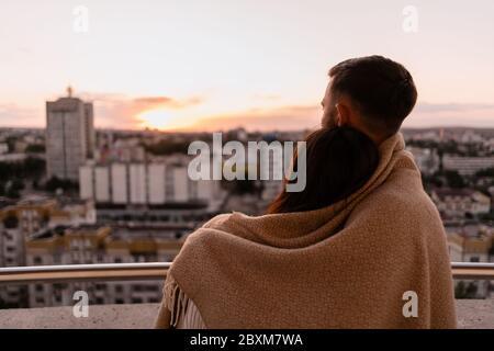 Primo piano ritratto, uomo e donna sorridenti l'uno all'altro al tramonto con la città sullo sfondo. Coppia momenti intimi romantici Foto Stock