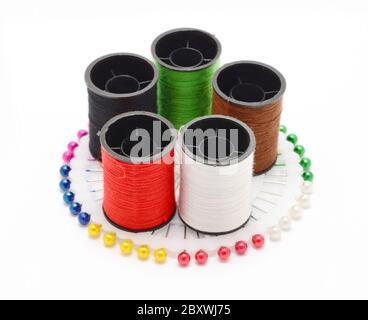 Set di fili da cucire colorati su ruota colorata di perni da cucire su sfondo bianco. Foto Stock