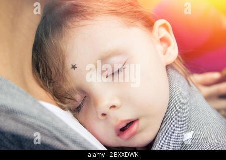 Bambina che dorme sul petto della madre in supporto di avvolgimento del bambino Foto Stock