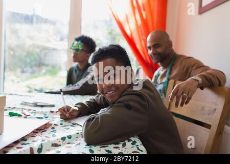 Ritratto ragazzo felice che scrive le schede di Natale al tavolo Foto Stock