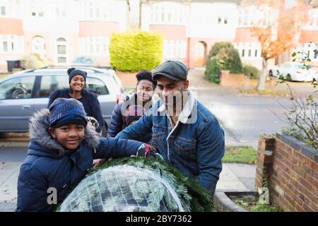 Ritratto felice famiglia che porta l'albero di Natale in vialetto Foto Stock