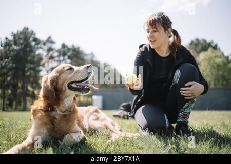 Cane e ragazza che giocano con palla all'aperto Foto Stock