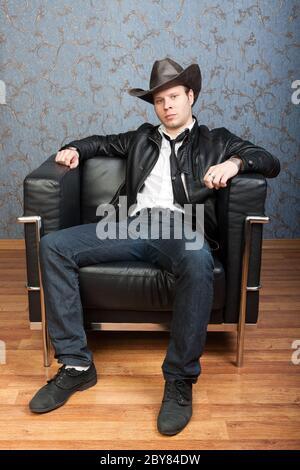 Un uomo elegante seduto in una sedia in pelle negli interni Foto Stock