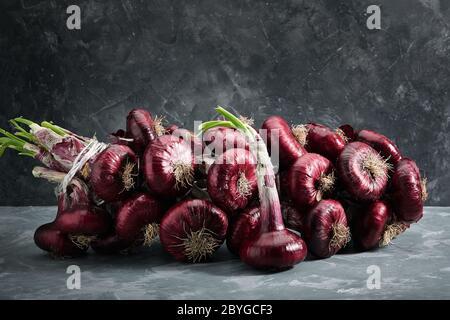 Cipolle rosse su sfondo grigio, verdure biologiche fresche. Cucina e cucina. Ingredienti per insalate, zuppe, piatti.