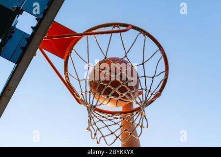 Street basket slam dunk concorrenza. Primo piano della palla che cade nel cerchio. Gioco urbano giovanile. Concetto di successo, punteggio e vincita