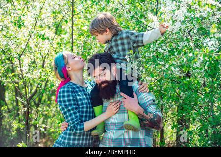 La famiglia cammina insieme attraverso il campo di fiori primaverili. Famiglia felice di trascorrere il tempo insieme in giardino. Famiglia a piedi in campo agricolo. Foto Stock