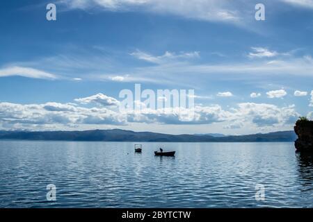 Pesca del pescatore da solo sul lago Ohrid in una giornata nuvolosa estiva, Città di Ohrid, Repubblica di Macedonia del Nord (FYROM)