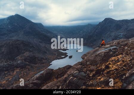 Concetto di stile di vita sportivo di viaggio. Uomo sopra una nubi nebbie, mattina paesaggio collinare. Vista sulla catena montuosa di Cullin con vista su un lago nell'Isola di S. Foto Stock