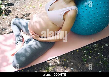 Bella giovane donna incinta che fa esercizio con fitness Pilates palla blu nel parco all'aperto. Seduta e relax su un tappetino rosa per yoga. Futuro attivo Foto Stock