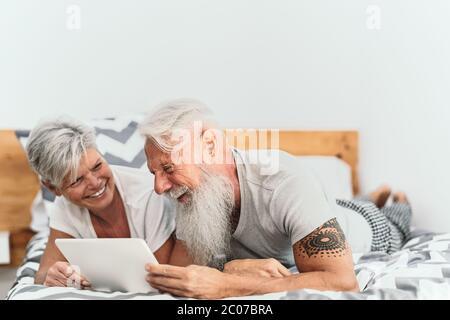 Felice coppia senior che usa il tablet digitale a letto - persone mature che hanno divertente tempo a letto insieme