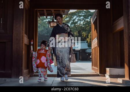 Madre e una piccola figlia in kimono tradizionale giapponese camminando attraverso una porta di legno al Santuario Meiji Jingu a Tokyo Giappone Foto Stock