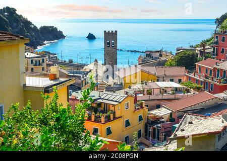 L'azzurro Mar Ligure e la costa della città di Monterosso al mare sulla Riviera Italiana delle Cinque Terre in Italia con la torre della chiesa in vista Foto Stock