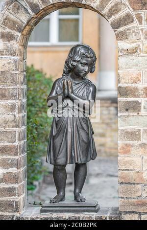 Antica statua di una bella bambina che prega nel parco del centro di Potsdam, Germania, ritratto, dettagli