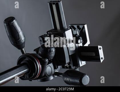 testa del treppiede inclinabile con panoramica a 3 vie su sfondo grigio Foto Stock