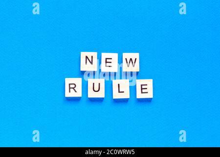 La NUOVA REGOLA è scritta in lettere di legno su sfondo blu. Nuovo concetto. Affari, legge, regole, aggiorna. Layout tflat. Op view.