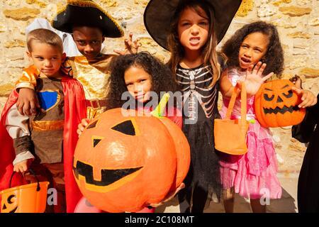 Gruppo di bambini carino in costume con ragazza tenere enorme zucca arancione Halloween Foto Stock