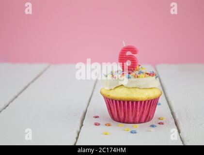 Buon compleanno Cup cake con rosa numero 6 candela su bianco tavola di legno per bambina Foto Stock