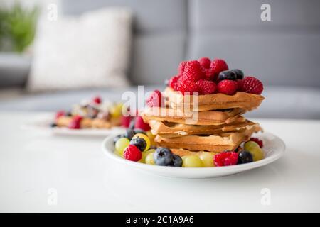 Dolce ragazzo di compleanno del bambino, mangiando waffle belgi con lamponi, mirtilli, cocnoci e cioccolato a casa