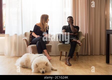 Uomo e donna che discutono seduti sulle poltrone del soggiorno con il cane che dormiva davanti. Foto Stock