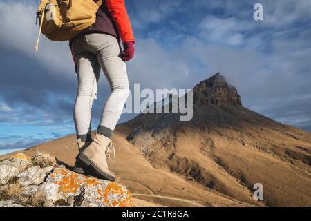 Primo piano dalla parte posteriore di una ragazza viaggiatore sullo sfondo dell'epico outdor rocce. Verticale sotto il nastro Foto Stock
