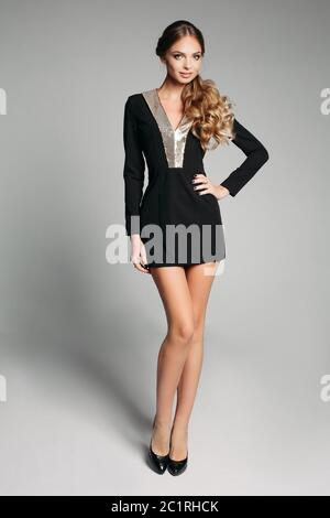 Donna bionda in mini abito nero con collare di pelliccia e i