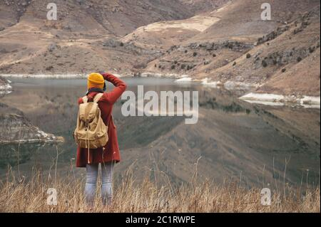 Un ritratto dalla parte posteriore di una ragazza viaggiatore scattare una foto sullo sfondo di un lago in montagna in autunno o in primavera Foto Stock