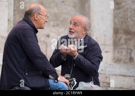 Due italiani parlano tra loro e fanno gesti tipici italiani sulla piazza del Popolo di Ascoli Piceno, Italia