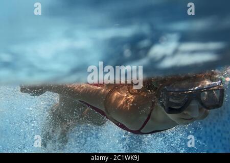 Bambina bionda che nuota in piscina blu Foto Stock