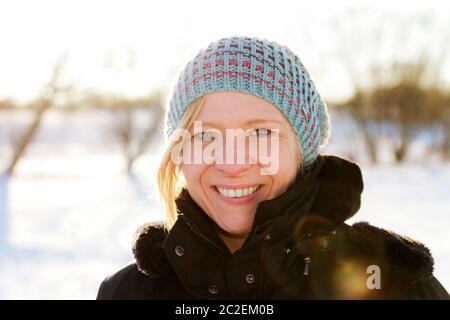 Donna bionda passeggiate all'aperto in un paesaggio innevato scena. Il tempo di Natale e in inverno il concetto di usura. Foto Stock