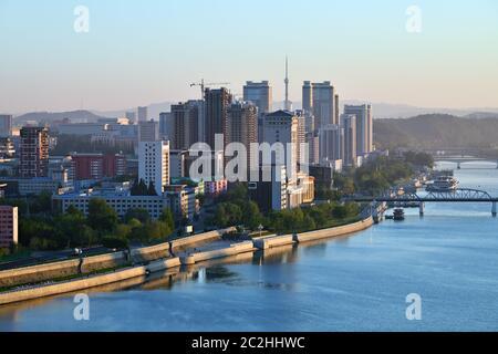 Alba a Pyongyang, Corea del Nord e Taedong fiume nella nebbia mattutina. Vista verso monte, moderno complesso residenziale e nuovo cantiere. Vi