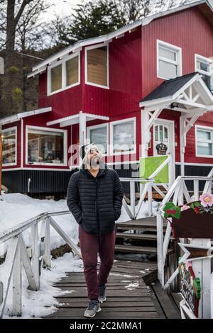 uomo che cammina di fronte a un bel tubo rosso in inverno. Tutto è coperto di neve. Foto Stock