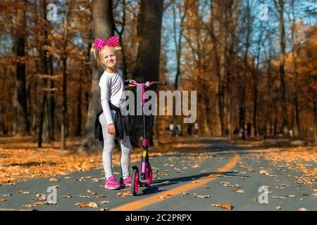 Carino adorabile ritratto ragazza scuola caucasica avendo divertimento cavalcare bici rosa calcio scooter in autunno oro parco della città o foresta fuori. Felice Foto Stock