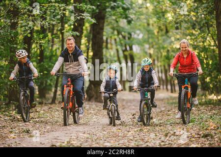 genitori e bambini in bicicletta sulla foresta. Giovane famiglia in abiti caldi in bicicletta nel parco autunnale. Famiglia mountain bike sulla foresta. Foto Stock