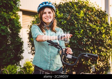 Ritratto di un cellulare allegro ragazza tenuta. Felice studente sorridente che usa l'app per la condivisione delle biciclette su smartphone all'aperto. Vita cittadina Foto Stock