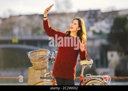 Una bella giovane donna con una bicicletta rossa retrò sta facendo una foto di se stessa nella città vecchia d'Europa sul fiume Reno emban