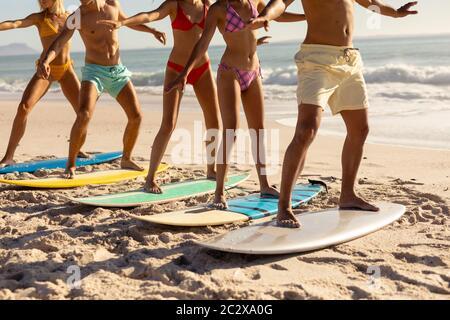 Gruppo multietnico di uomini e donne, surf sulla spiaggia