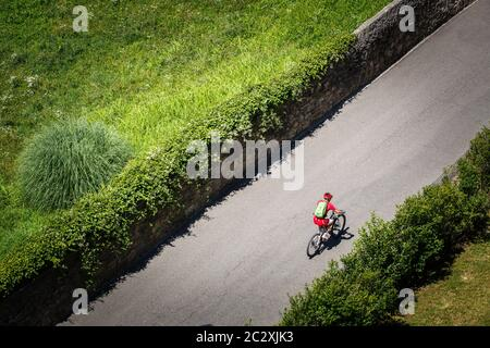 il ciclista corre una mountain bike con sospensione completa lungo una strada asfaltata lungo le verdi piantagioni fino. Vestito in velluto Foto Stock