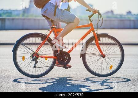 Giovane donna che corre in bicicletta sulla strada cittadina. Ragazza con con logo reporter, fotocamera e zaino guida una bicicletta. Clima caldo e soleggiato