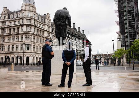 Gli ufficiali di polizia si trovano in guardia alla statua di Winston Churchill, che si trova in Piazza del Parlamento dopo aver trascorso diversi giorni coperti da un protettivo