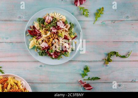 Insalata verde fresca con rucola, cavolfiore, kale e pistacchi su sfondo di legno. Cibo vegetariano.