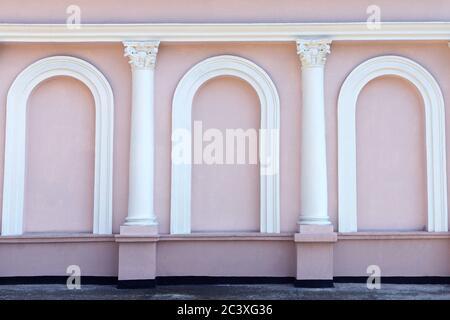 Facciata rosa senza finestre dell'edificio con colonne e archi bianchi. Esterno bellissimo. Sfondo, sfondo