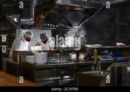 maschera sul viso dello chef in un ristorante: cucina in una cucina aperta, un cliente vede il lavoro durante una pandemia