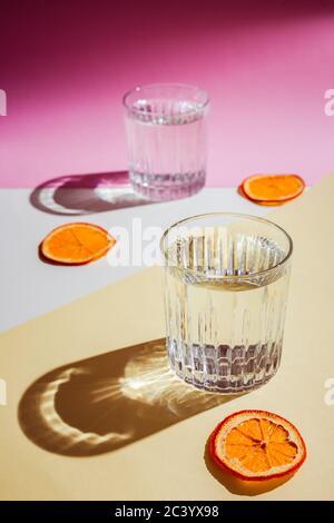 Una foto verticale molto luminosa di due rocce bicchieri d'acqua, luce dura diretta con ombre dure, scaglie di arancio