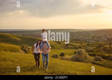 Famiglia amorevole con bambino godendo la loro vacanza estiva in montagna. Genitori e figlia in campagna al tramonto Foto Stock