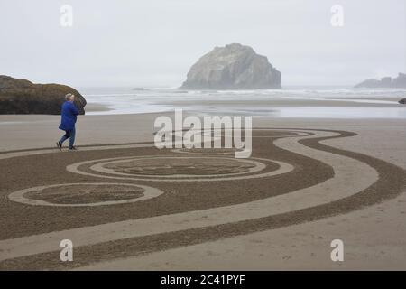 Una donna che cammina un cerchio nel labirinto di sabbia a Face Rock Beach a Bandon, Oregon, Stati Uniti.